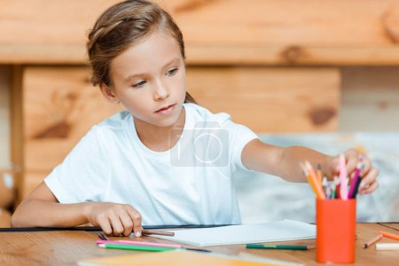 Photo for Selective focus of cute kid taking color pencils - Royalty Free Image