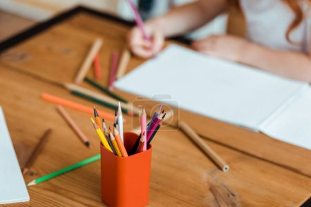 Photo for Selective focus of color pencils near kid and paper on table - Royalty Free Image