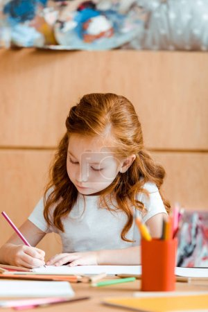 Photo for Selective focus of cute redhead child holding color pencil while drawing on paper - Royalty Free Image