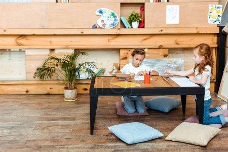 Photo pour De beaux enfants assis sur des oreillers et dessinant au bureau - image libre de droit