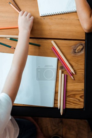Photo for Top view of kid taking color pencil near child - Royalty Free Image