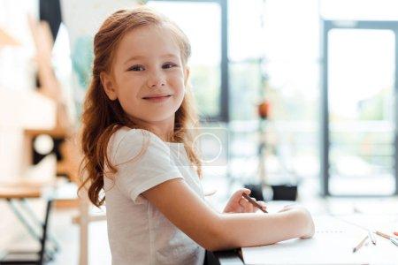 Photo pour Un enfant joyeux à tête rouge souriant et regardant la caméra - image libre de droit