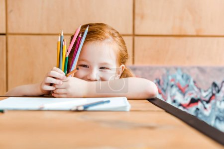 Photo pour Foyer sélectif de sourire rousse enfant tenant crayons de couleur - image libre de droit