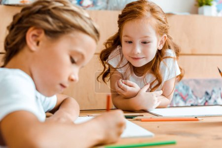 Photo for Selective focus of cute redhead kid looking at adorable child drawing on paper - Royalty Free Image