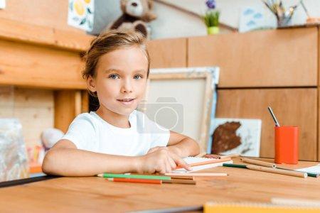 Photo pour Foyer sélectif d'enfant heureux souriant et regardant la caméra à l'école d'art - image libre de droit
