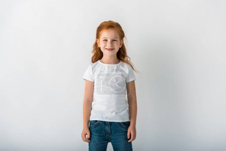 Photo for Smiling redhead child looking at camera on white - Royalty Free Image