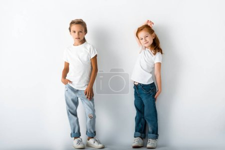 Photo for Cute kids in denim jeans standing on white - Royalty Free Image