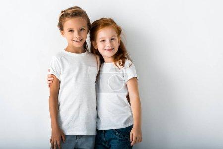 Photo pour Des enfants joyeux serrent dans leurs bras tout en restant sur le blanc - image libre de droit