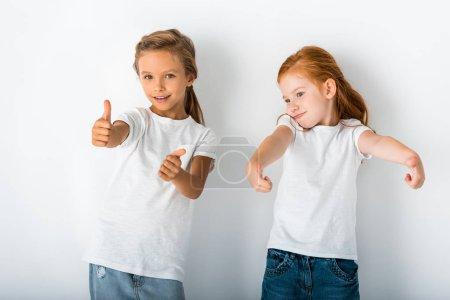 Foto de Niños adorables sonriendo y mostrando pulgares sobre blanco. - Imagen libre de derechos