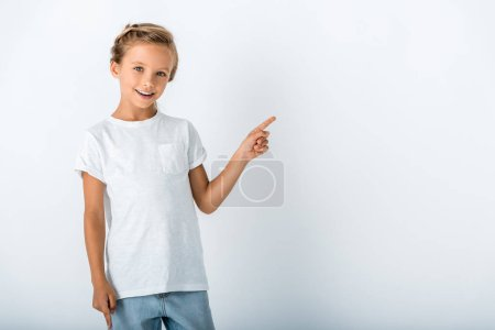 Photo for Cheerful kid looking at camera and pointing with finger on white - Royalty Free Image