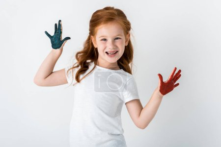 Photo pour Enfant rousse joyeux avec de la peinture sur les mains debout isolé sur blanc - image libre de droit