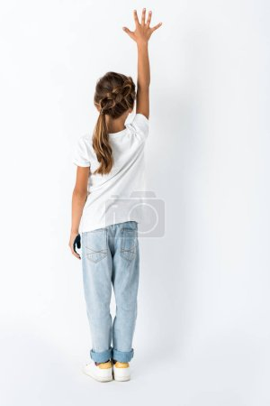 Photo for Back view of kid with hand above head standing on white - Royalty Free Image