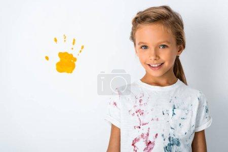 Photo pour Heureux enfant souriant près de jaune impression à la main sur blanc - image libre de droit