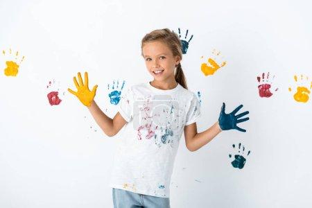 Photo pour Enfant avec de la peinture bleue et jaune sur les mains près des empreintes de main sur blanc - image libre de droit