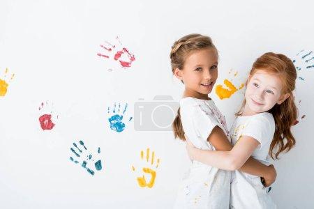 cheerful kids hugging near hand prints on white