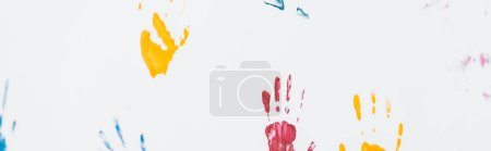 Photo for Panoramic shot of yellow, blue and red hand prints on white - Royalty Free Image