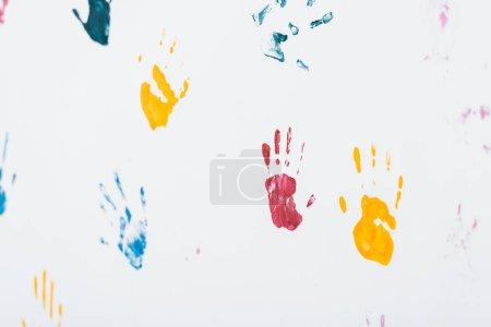 Photo pour Mise au point sélective d'empreintes de mains jaunes, bleues et rouges sur blanc - image libre de droit