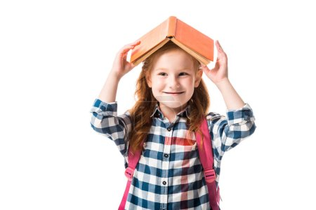 Photo for Cheerful redhead pupil holding orange book above head isolated on white - Royalty Free Image
