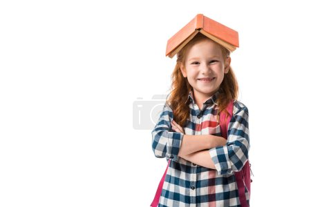 cheerful redhead pupil with orange book on head standing with crossed arms isolated on white