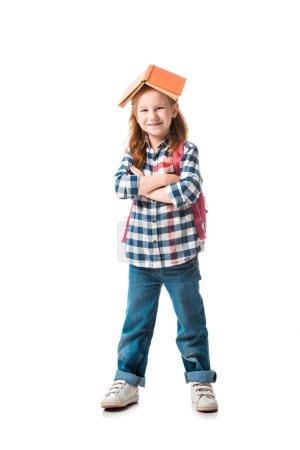 Photo pour Jeune garçon joyeux à tête rouge avec livre orange sur la tête debout avec les bras croisés isolés sur blanc - image libre de droit