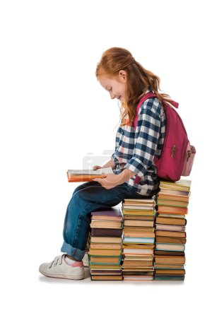 Photo for Cheerful redhead schoolkid smiling while sitting on books isolated on white - Royalty Free Image