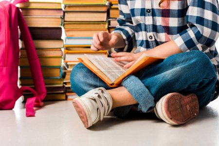 Photo for Cropped view of schoolkid sitting near books and pink backpack on white - Royalty Free Image