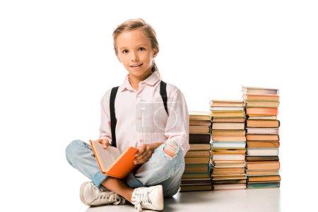 Photo pour Heureux enfant assis avec les jambes croisées près des livres sur le blanc - image libre de droit