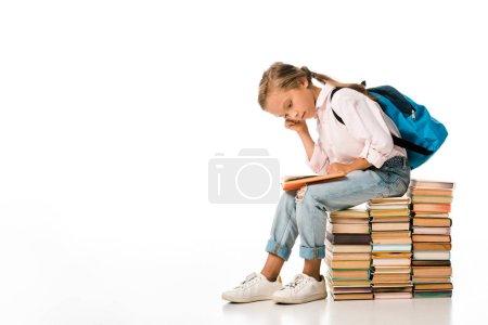 Photo pour Écolier mignon assis sur des livres et lisant sur du blanc - image libre de droit