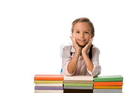 Photo for Positive schoolkid looking at camera near colorful books isolated on white - Royalty Free Image