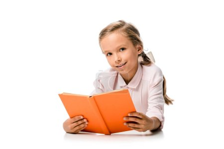Photo for Happy schoolkid holding orange book and smiling on white - Royalty Free Image