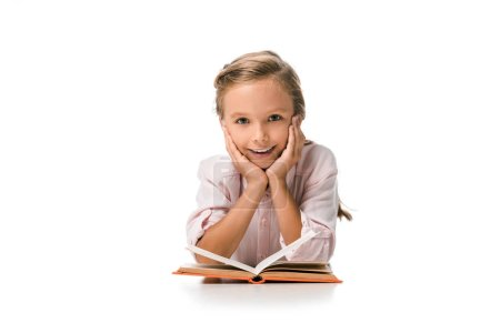 Photo for Happy schoolkid smiling near book on white - Royalty Free Image