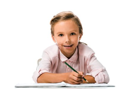 Photo for Cheerful schoolkid smiling and holding pencil near notebook isolated on white - Royalty Free Image