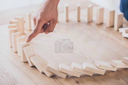 Photo pour Vue recadrée du gestionnaire de risques arrêtant l'effet domino des blocs de bois tombants - image libre de droit