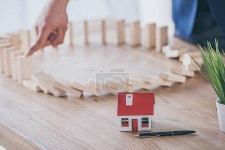 Photo pour Vue partielle du gestionnaire des risques blocage effet domino de la chute de blocs de bois près du modèle de maison - image libre de droit