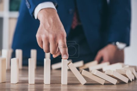 Photo for Partial view of risk manager blocking domino effect of falling wooden blocks - Royalty Free Image