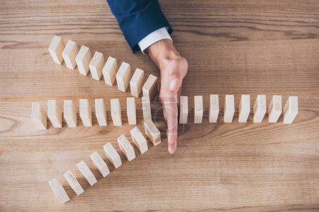 Photo pour Vue recadrée du gestionnaire de risques protégeant les blocs de bois contre l'effet domino - image libre de droit
