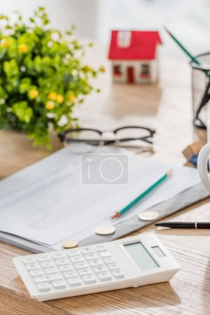 Photo for Selective focus of calculator near coins, paper, glasses, green plant and house model on wooden table - Royalty Free Image