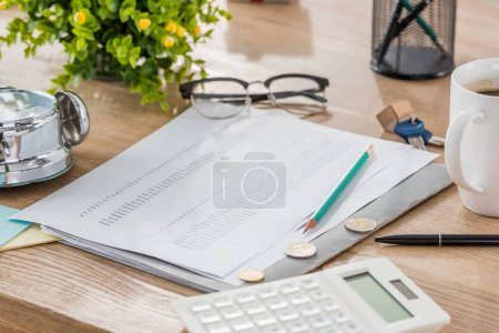 Photo pour Calculatrice près des pièces de monnaie, papier, tasse à café, verres, plantes vertes et maquette de maison sur table en bois - image libre de droit