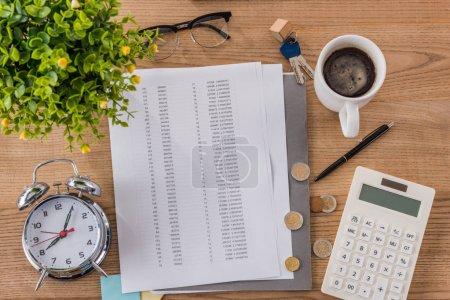 Photo pour Vue du dessus de la table en bois avec document, tasse à café, réveil, clés de la maison, calculatrice et plante verte - image libre de droit