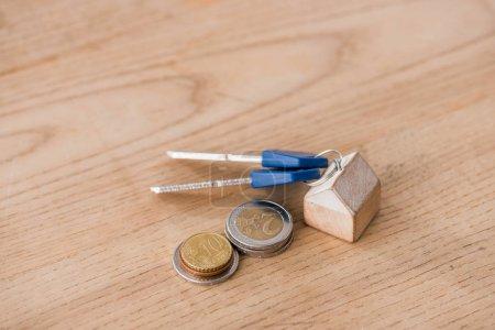 Photo pour Clés avec linge de maison jouet près des pièces d'or et d'argent sur table en bois - image libre de droit