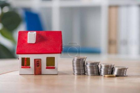 Photo pour Maquette de maison près de piles de pièces d'or et d'argent sur une table en bois - image libre de droit