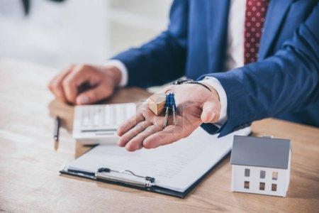 Photo pour Vue partielle d'un homme d'affaires sur son lieu de travail tenant des clés près d'un modèle de maison, d'un presse-papiers et d'une calculatrice - image libre de droit