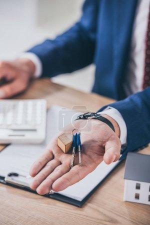 Photo pour Vue partielle d'un homme d'affaires sur son lieu de travail montrant des clés près d'un modèle de maison, d'un presse-papiers et d'une calculatrice - image libre de droit