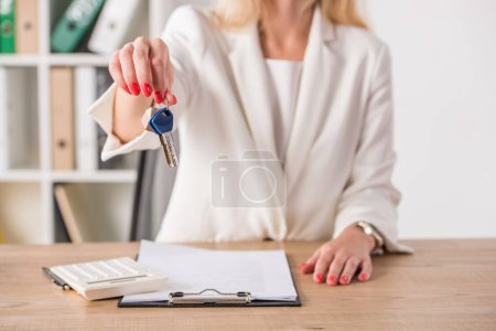 Photo for Partial view of businesswoman at workplace holding keys and touching house model near clipboard and calculator - Royalty Free Image