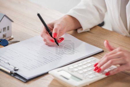 Photo pour Vue en coupe d'une femme d'affaires utilisant une calculatrice et écrivant un contrat près de la maison modèle et clés - image libre de droit
