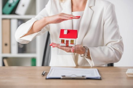 Photo for Partial view of businesswoman holding and covering house model with hand near clipboard - Royalty Free Image