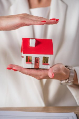 partial view of businesswoman holding and covering house model with hand
