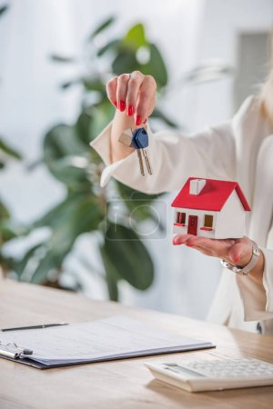 Photo for Partial view of businesswoman showing house model and keys near clipboard and calculator - Royalty Free Image