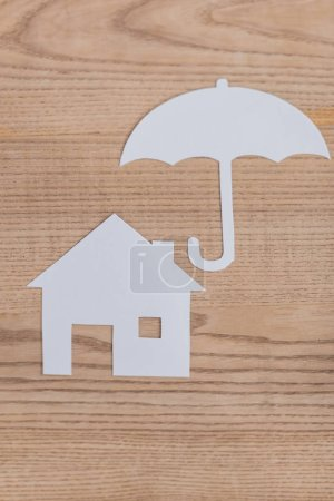 top view of white paper cut house and umbrella on wooden desk