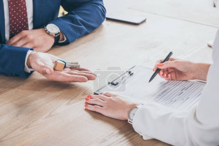 Photo for Partial view of businessman holding house keys near man signing agreement - Royalty Free Image
